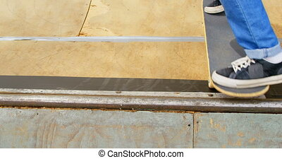 Close-up of young man doing skateboard trick on skateboard ramp at skateboard court 4k
