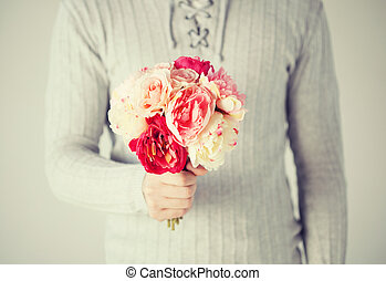 man holding bouquet of flowers - close up of young man ...