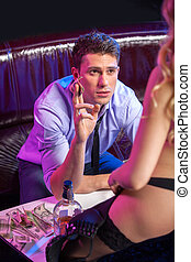 Close up of young man in strip bar. Giving tips to sexy blond striptease dancer
