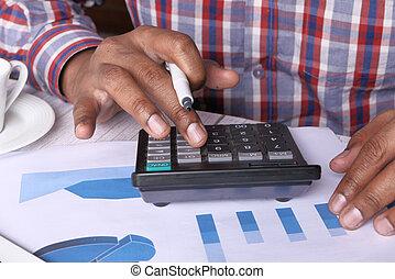 Close up of young man using calculator
