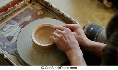 Close-up of young man's hands molding clay into ceramic bowl...
