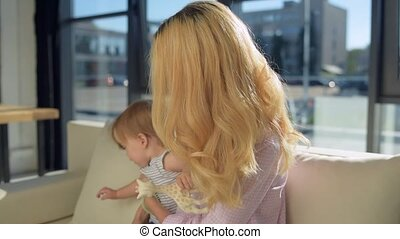 Close up of young mother with the child sitting on the sofa