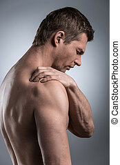 Close-up of young shirtless man with shoulder pain. young...
