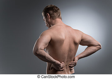 Close-up of young shirtless man with back pain. young man...