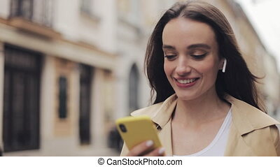 Close Up of Young Smiling Pretty Caucasian Girl Wearing Earphones Walking on the Street Holding Phone in Her Hand and Typing.