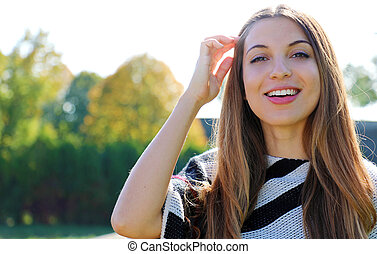 Close up of young smiling woman outdoor looking at camera in spring