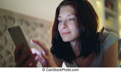 Close-up of young smiling woman using smartphone lying in bed at home at night