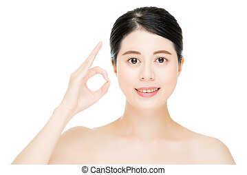 Close up of young smiling woman with finger ok gesture