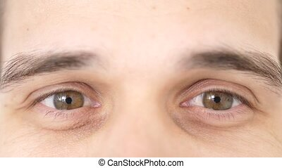 Close up of young successful male brown eyes smiling looks at camera. slow motion.