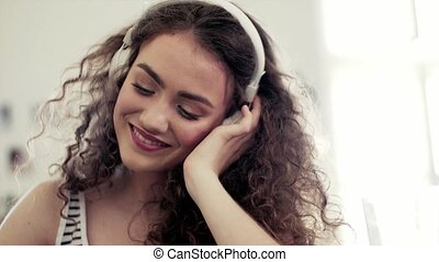 Close-up of young teenage girl with headphones sitting indoors, listening to music.