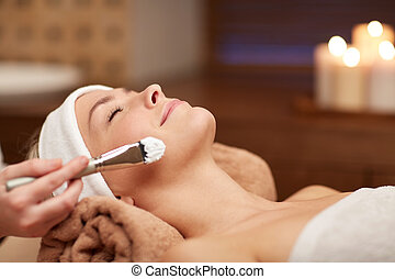 close up of young woman and cosmetologist in spa - people,...