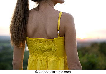 Close up of young woman back in yellow summer dress standing outdoors.