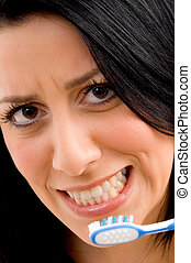 close up of young woman brushing her teeth with white...