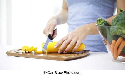 close up of young woman chopping squash at home - healthy...