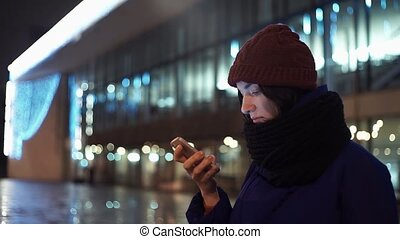 Close up of young woman dressed in warm jacket using smartphone. City at night.