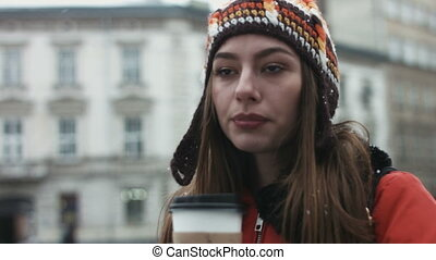 Close-up of young woman drinking take away coffee outdoors and looking for her friend from the crowd. Attractive female waiting for her partner.