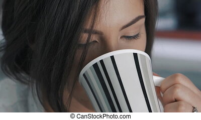 Close up of young woman drinks tea at office