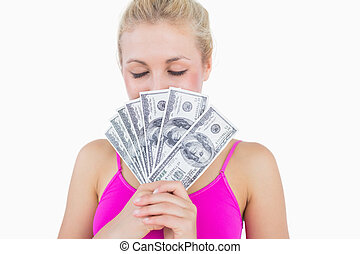 Close-up of young woman holding fanned banknotes in front of face with eyes closed