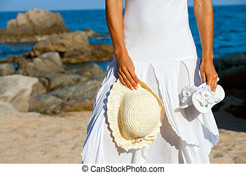 Young woman holding hat and flip flops on beach.