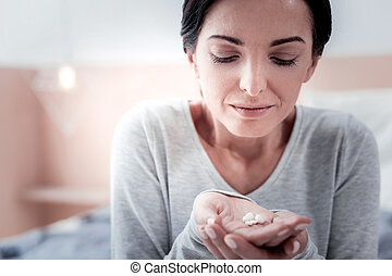 Close up of young woman holding pills in her hand