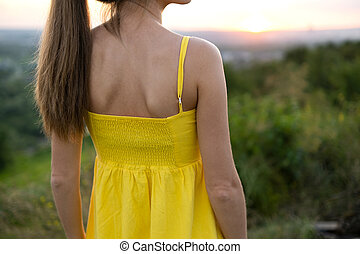 Close up of young woman in yellow summer dress standing outdoors.