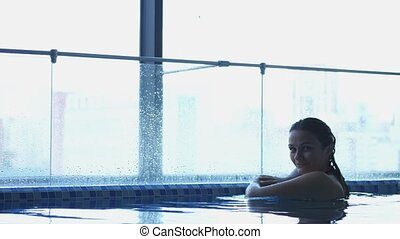 Close up of an young woman is enjoying and having relax in swimming pool in a luxury wellness center.