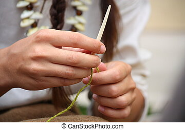 Close up of young woman knitting with bone needles