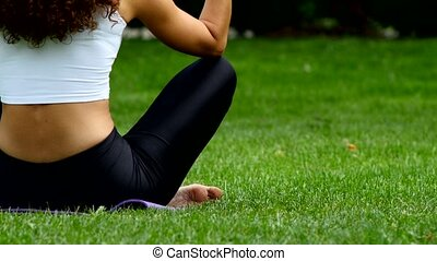 Close up of young woman meditating sitting in a park. Yoga.
