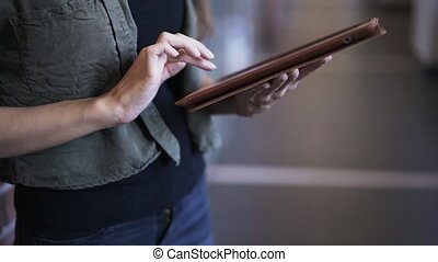 Close up of young woman s hands using tablet, tilt up