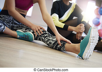 Close up of young woman stretching legs
