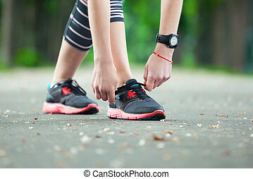 Close up of young woman tying her laces before a run. - Shot...