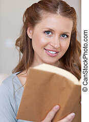 Close up of young woman with a book