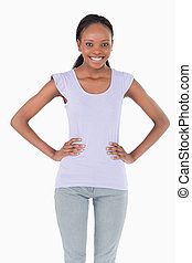Close up of smiling young woman with arms akimbo on white background