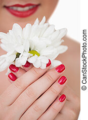 Close-up of young woman with red lips and red painted nails holding flowers over white background
