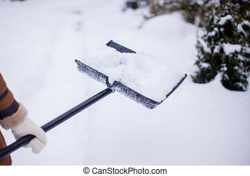 Close Up Of young woman's hands Shovelling Snow From Path