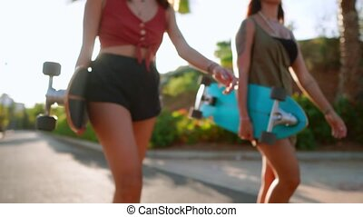 Close-up of young women carry skateboards in their hands and communicate with a smile. Boards for riding in the hands in the sun.
