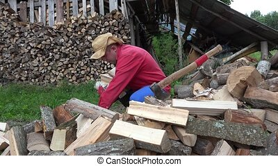 young worker man gather wood in hand at village yard. 4K