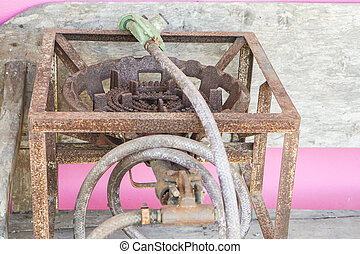 close up old and rusty gas stove with supply gas pipes