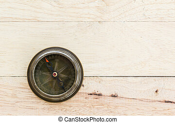 Close up old compass on wood .