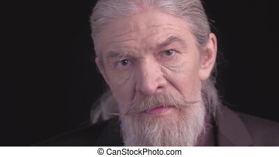 Close up. Old man with long beard in dark business clothes looking at camera in semi-lit room on black. Camera slide. Toned footage. Prores 422.