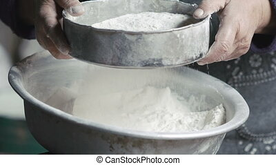 Close up old wrinkled hands sifting flour into bowl on table. Slow motion