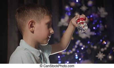 Close up. On a Christmas party, a little boy is playing with a snow globe inside which is santa