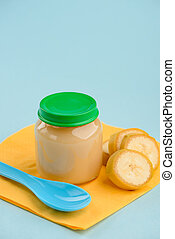 Close up on a jar of banana puree, slices and spoon