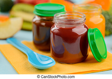 Close up on a little jars of fruit puree and spoon
