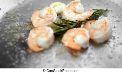 Close up on a shrimps fry on a frying pan with a garlic and...