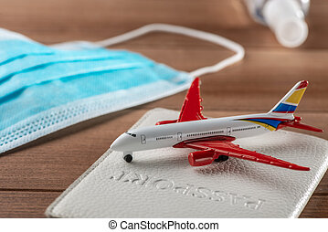 Close-up on airplane toy, passport and medical face mask on the table