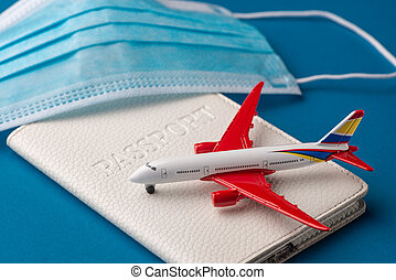 Close-up on airplane toy, passport and surgical face mask on blue background
