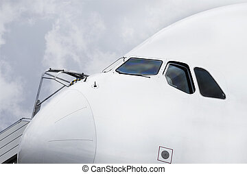 Close up on an airliner cockpit and cloudy sky - Close up of...