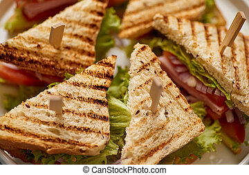 Close up on appetizing fresh and healthy grilled club sandwiches with ham and cheese