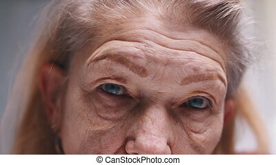 Close up on blue sad eyes of an elderly woman with wrinkled skin. Depression at old age. High quality 4k footage